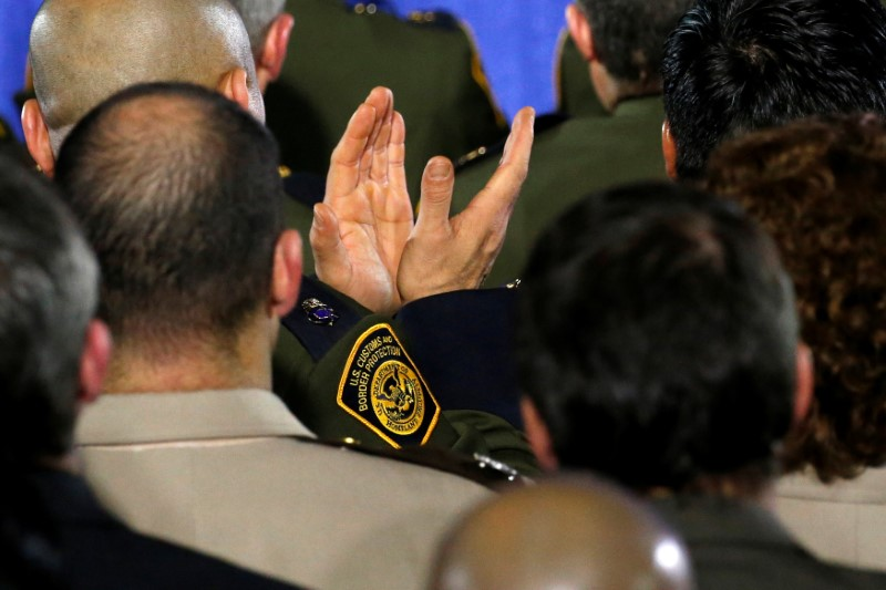 A U.S. Customs and Border Protection agent applauds President Donald Trump's remarks at Homeland Security headquarters in Washington, U.S. January 25, 2017. REUTERS/Jonathan Ernst