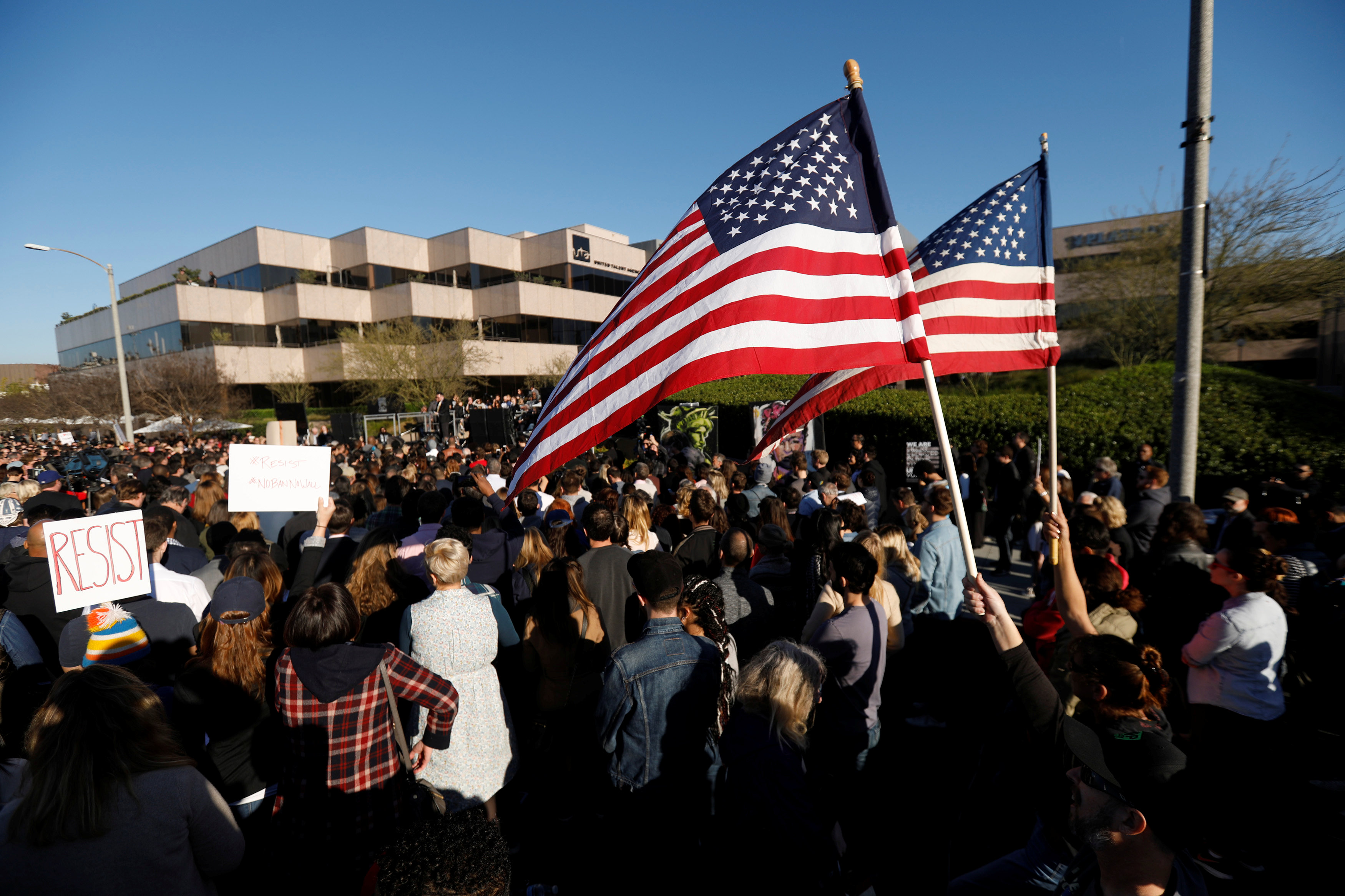 """Supporters of U.S. President Donald Trump wave U.S. flags during a """"United Voices"""" rally hosted by United Talent Agency in Beverly Hills, California U.S"""
