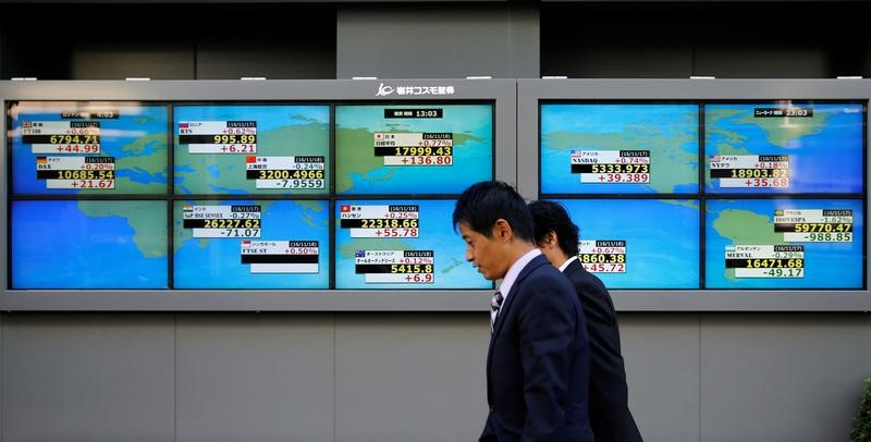 Men walk past an electronic board showing Japan's Nikkei average outside a brokerage in Tokyo, Japan,