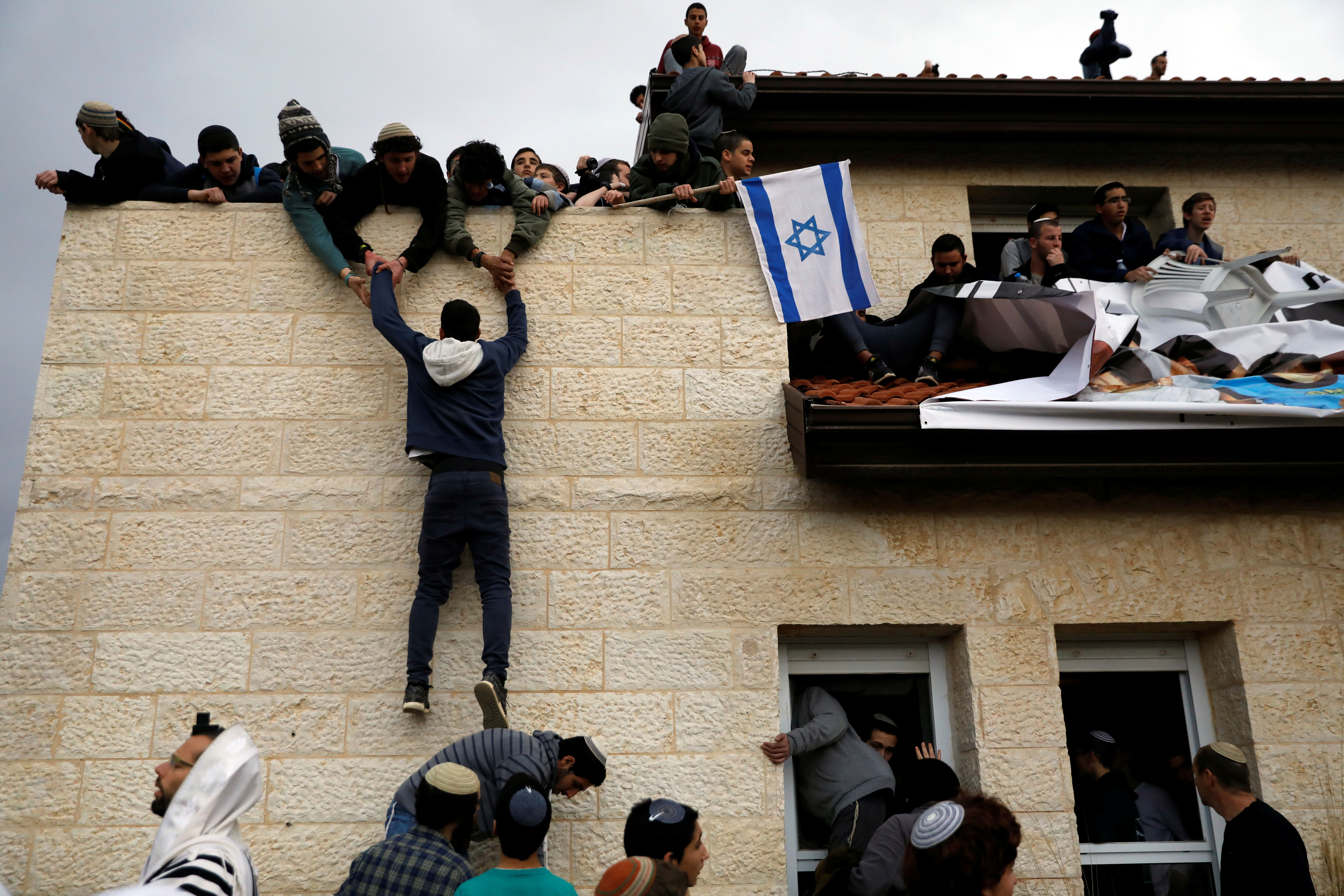 A pro-settlement activist climbs onto a rooftop of a house to resist evacuation of some houses in the settlement of Ofra in the occupied West Bank, during an operation by Israeli forces to evict the houses. REUTERS/Ronen Zvulun