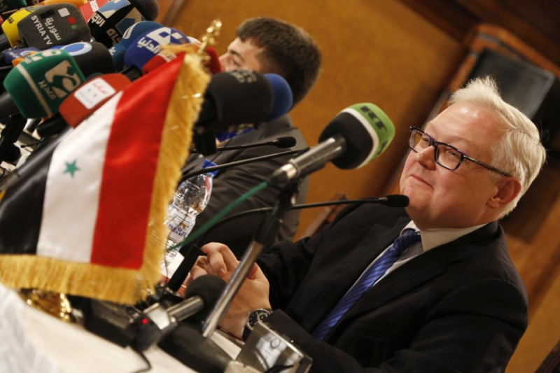 Russia's Deputy Foreign Minister Sergei Ryabkov sits near the Syrian national flag as he addresses a news conference in Damascus in this file photo dated June 28, 2014. REUTERS/Omar Sanadiki