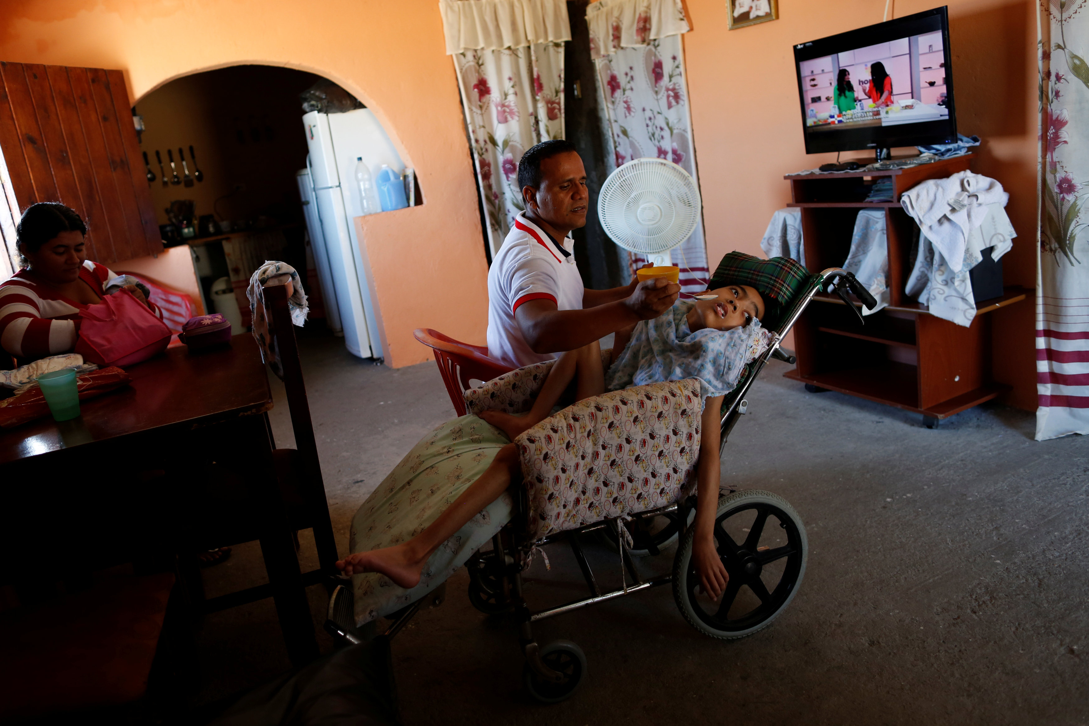 Miguel Anton (C) feeds his son Jose Gregorio Anton, 11, a neurological patient being treated with anticonvulsants, at their house in La Guaira, Venezuela February 20, 2017. REUTERS/Carlos Garcia Rawlins