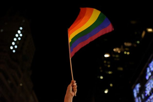 """An activist waves a rainbow flag during the """"Queer and Trans Dance Party"""" in protest of U.S. President Donald Trump outside of Trump Tower in Manhattan, New York, U.S., February 26, 2017. REUTERS/Darren Ornitz"""