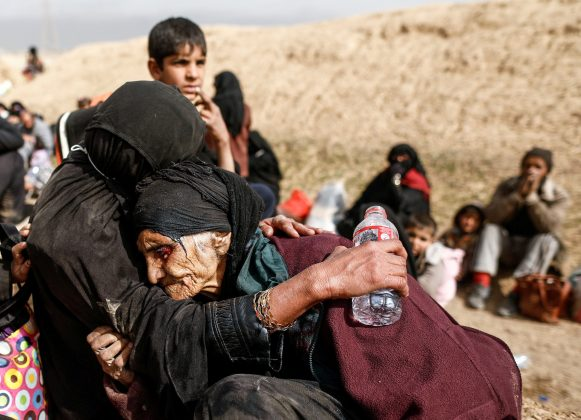 Khatla Ali Abdullah, 90, is embraced as she flees her home as Iraqi forces battle with Islamic State militants in western Mosul. REUTERS/Zohra Bensemra