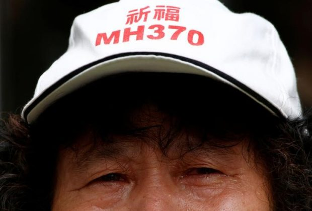 "A family member of a passenger aboard Malaysia Airlines flight MH370 which went missing in 2014 reacts during a protest outside the Chinese foreign ministry in Beijing, July 29, 2016. The hat reads ""Pray for MH370"" REUTERS/Thomas Peter"