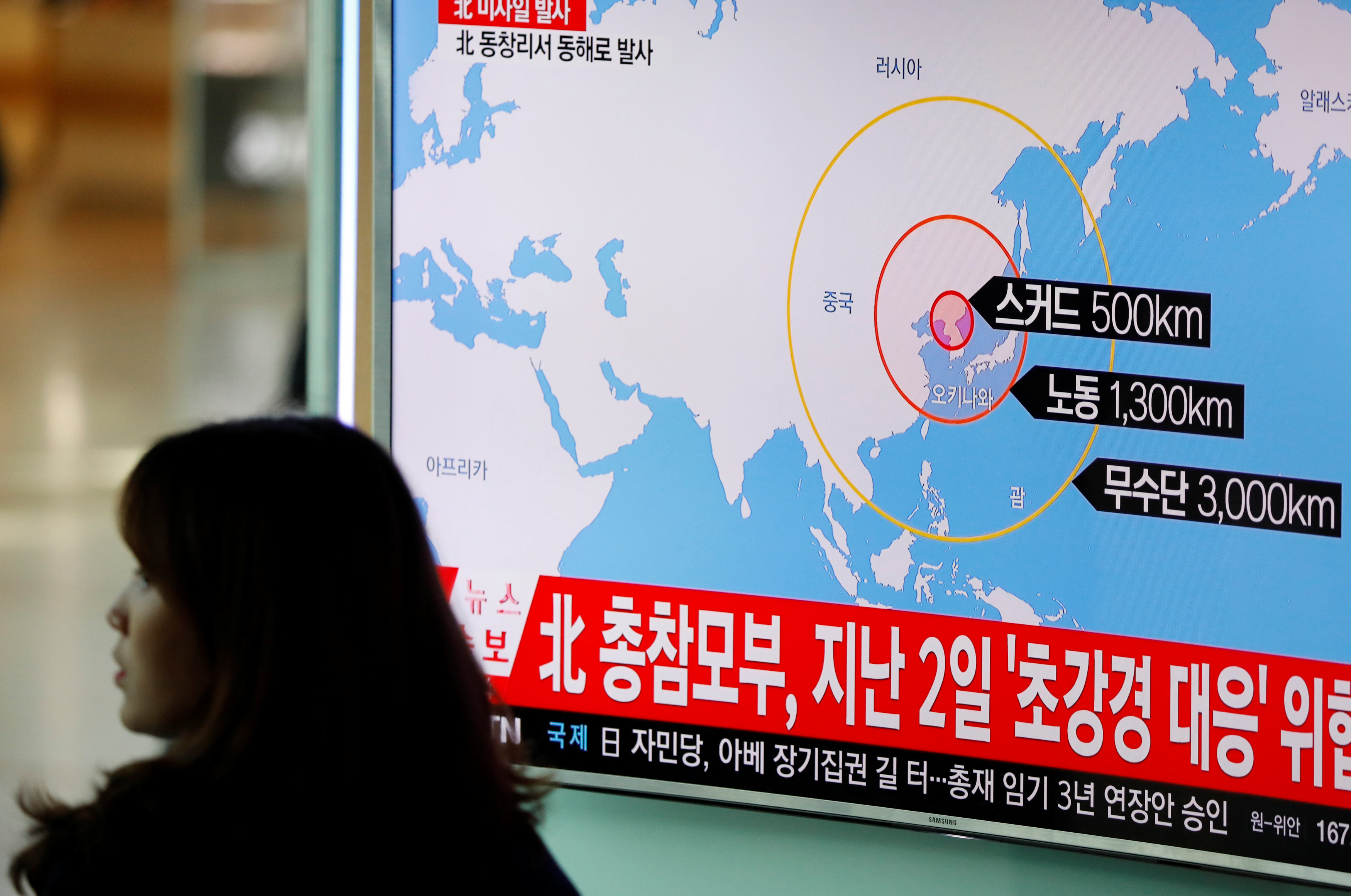 A woman walks past a television broadcasting a news report on North Korea firing ballistic missiles, at a railway station in Seoul, South Korea,
