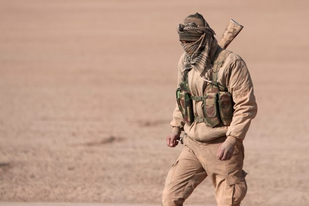 An Syrian Democratic Forces (SDF) fighter walks with his weapon in northern Raqqa province, Syria