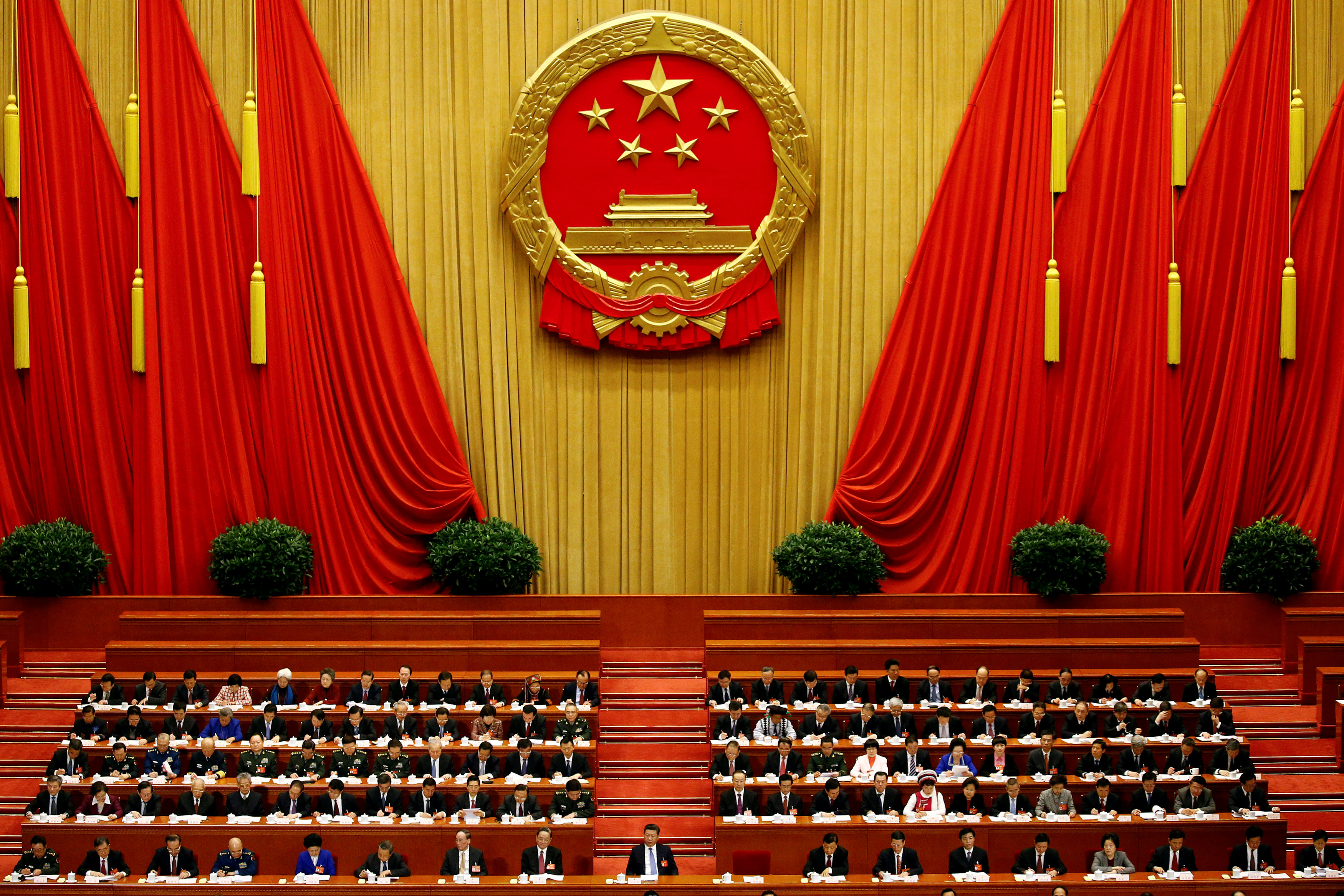 China's President Xi Jinping and other delegates listen as China's Premier Li Keqiang (not pictured) delivers a government work report during the opening session of the National People's Congress at the Great Hall of the People in Beijing. REUTERS/Damir Sagolj