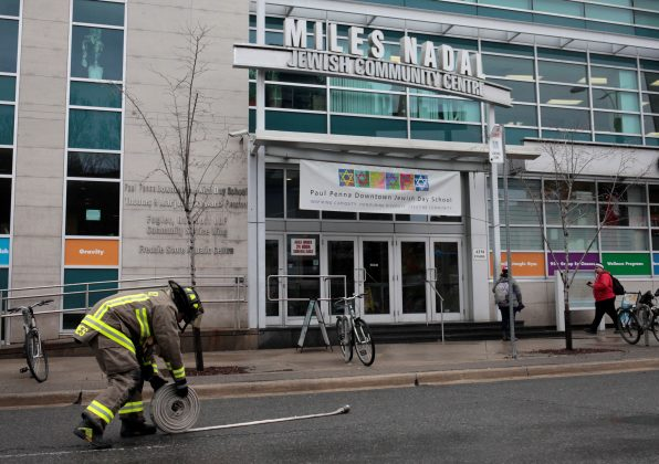 A firefighter rolls up a hose after a threat made to the Miles Nadal Jewish Community Centre was deemed a hoax in Toronto, Ontario, Canada, March 7, 2017. REUTERS/Chris Helgren
