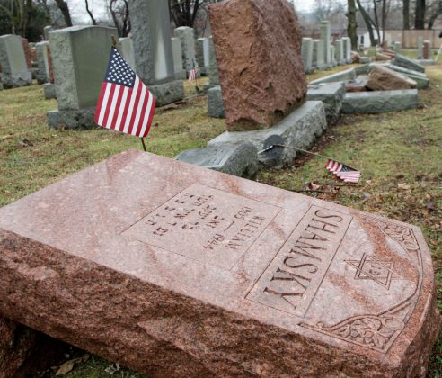 An American flag still stands next to one of over 170 toppled Jewish headstones at Chesed Shel Emeth Cemetery in University City, Missouri. REUTERS/Tom Gannam
