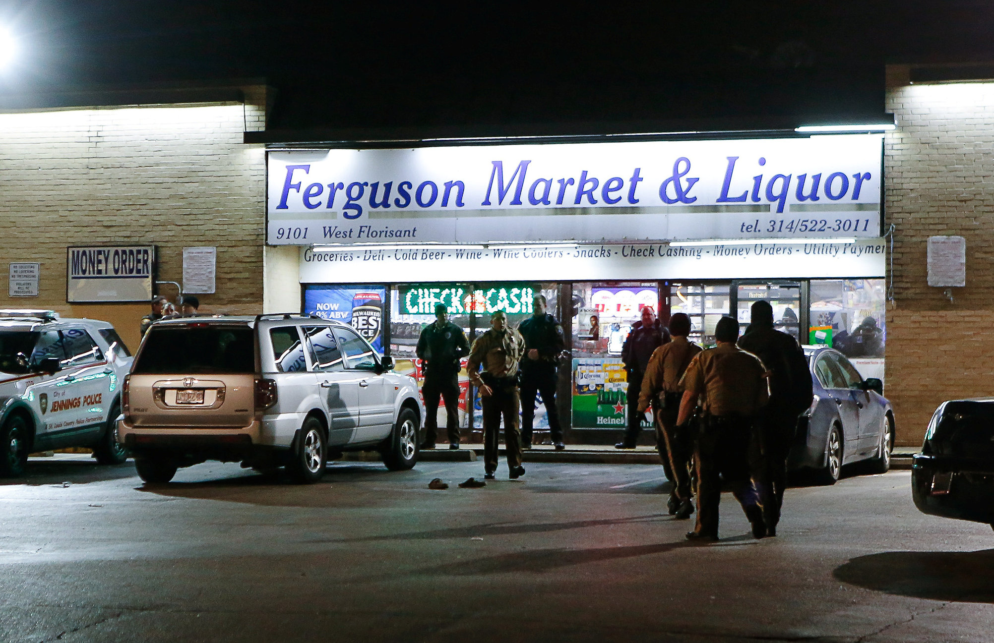 Police line up in front of the Ferguson Market Liquor during a protest, following a release of previously undisclosed video of Michael Brown