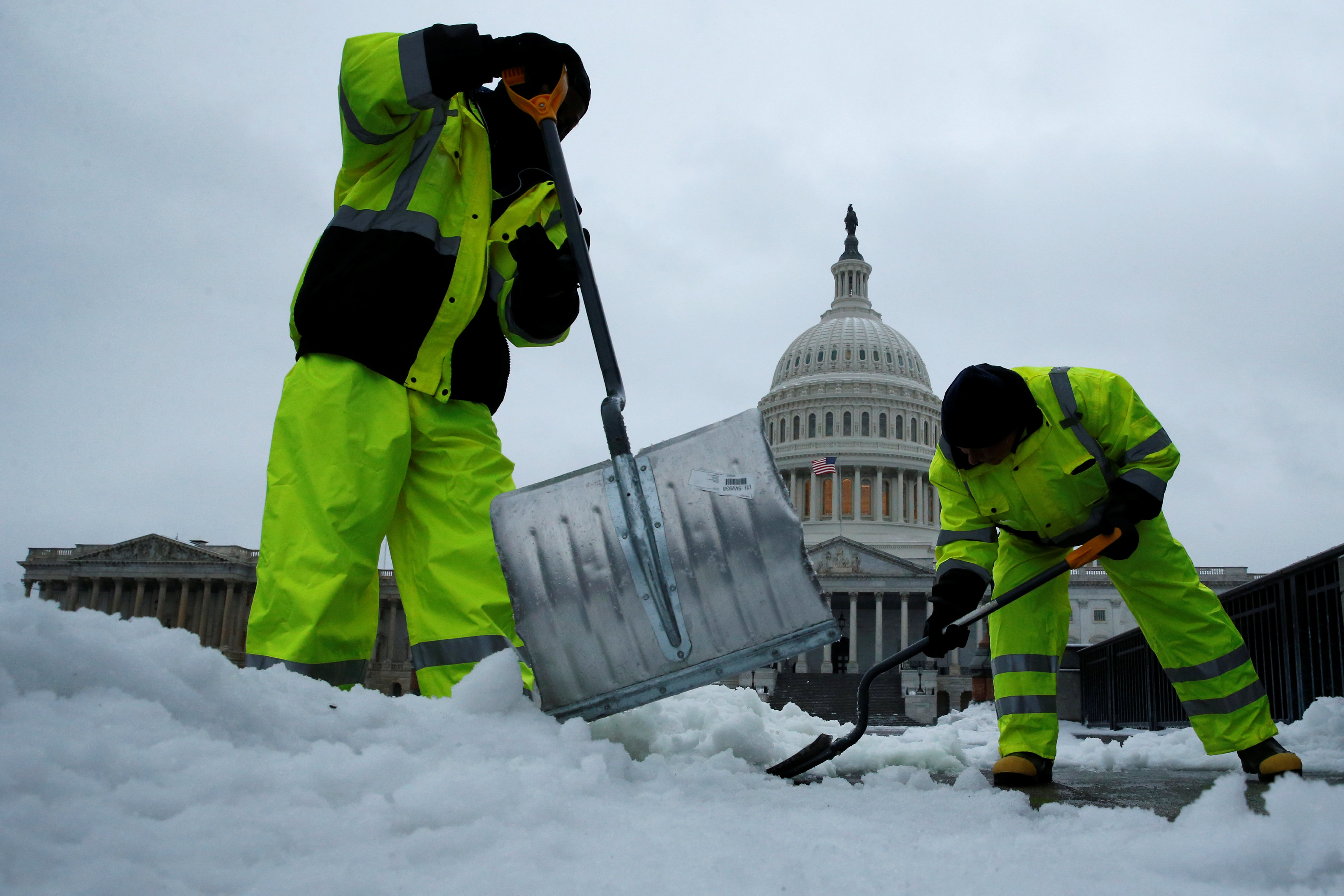 Workers clear frozen precipitation from a walkway at the U.S. Capitol in Washington, U.S., March 14, 2017. REUTERS/Jonathan Ernst