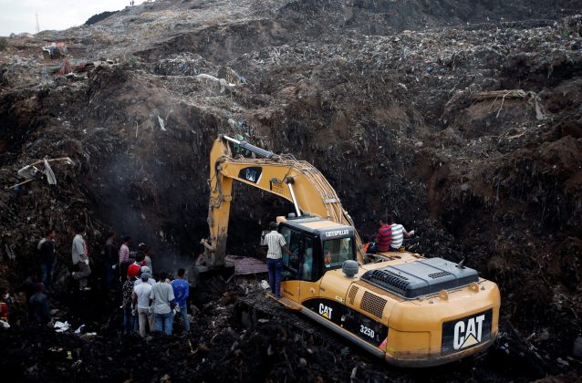 Rescue workers watch as excavators dig into a pile of garbage in search of missing people following a landslide when a mound of trash collapsed on an informal settlement at the Koshe garbage dump in Ethiopia's capital Addis Ababa. REUTERS/Tiksa Negeri