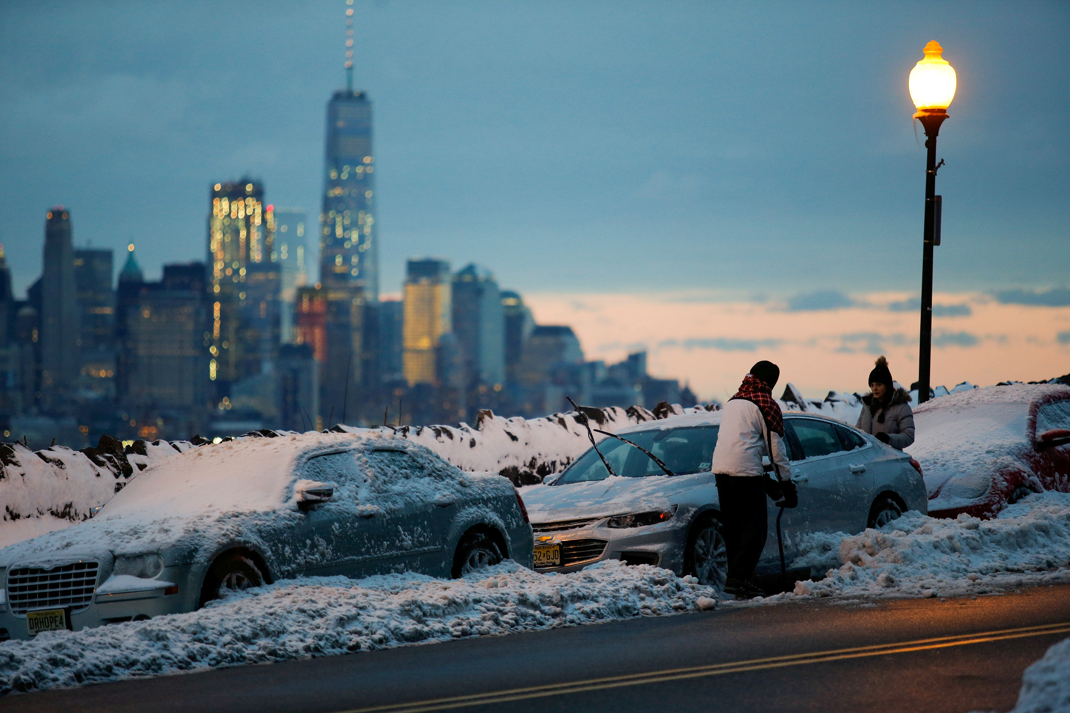 Residents clear their cars and street of snow in Weehawken, New Jersey, as the One World Trade Center and lower Manhattan are seen after a snowstorm in New York, U.S. March 14, 2017. REUTERS/Eduardo Munoz