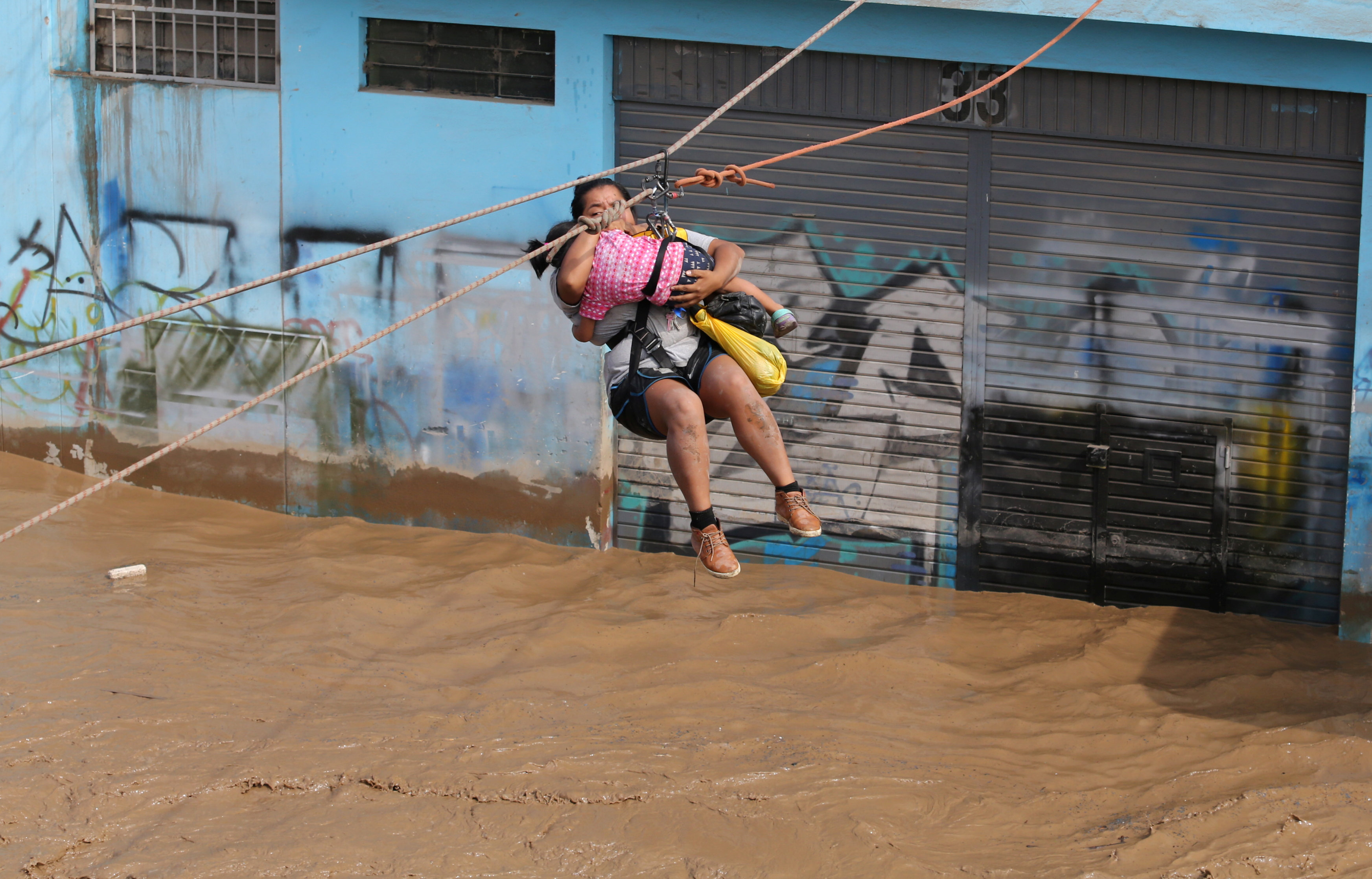 A woman and a child are evacuated with a zip line after the Huayco river overflooded its banks sending torrents of mud and water rushing through the streets in Huachipa, Peru, March 17, 2017. REUTERS/Guadalupe Pardo