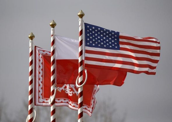 U.S. (R to L), Poland's flags and jack of the President of Poland are seen during the inauguration ceremony of bilateral military training between U.S. and Polish troops in Zagan, Poland,