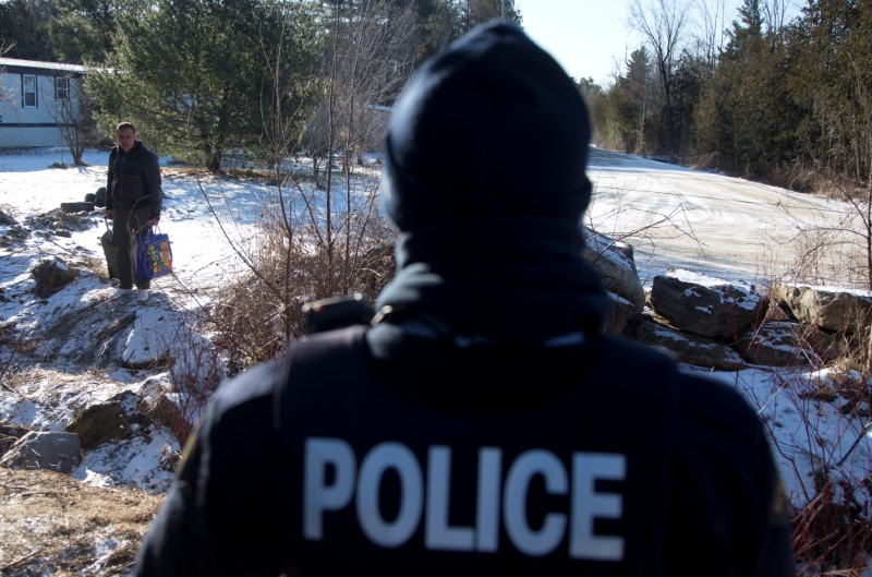 A man is confronted by a Royal Canadian Mounted Police officer as he prepares to cross the U.S.-Canada border leading into Hemmingford, Quebec.