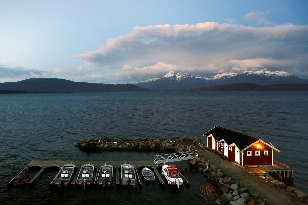 General view of a small harbour and snow-capped mountains in Bals-Fiord, north of the Arctic Circle, near the village of Mestervik in northern Norway.