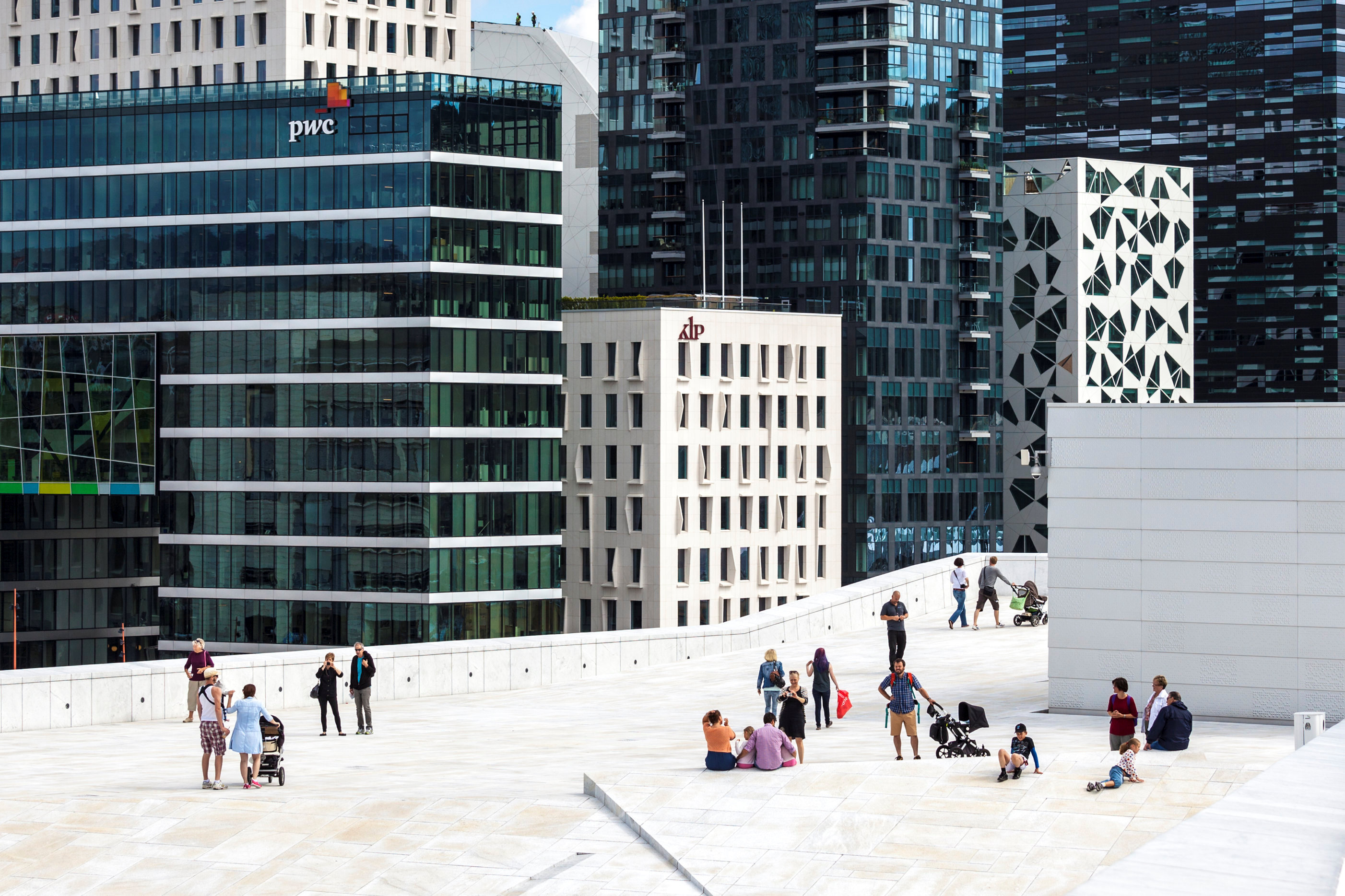 People stand on the roof of the Opera House, with buildings of The Barcode Project in the background, in Oslo, Norway