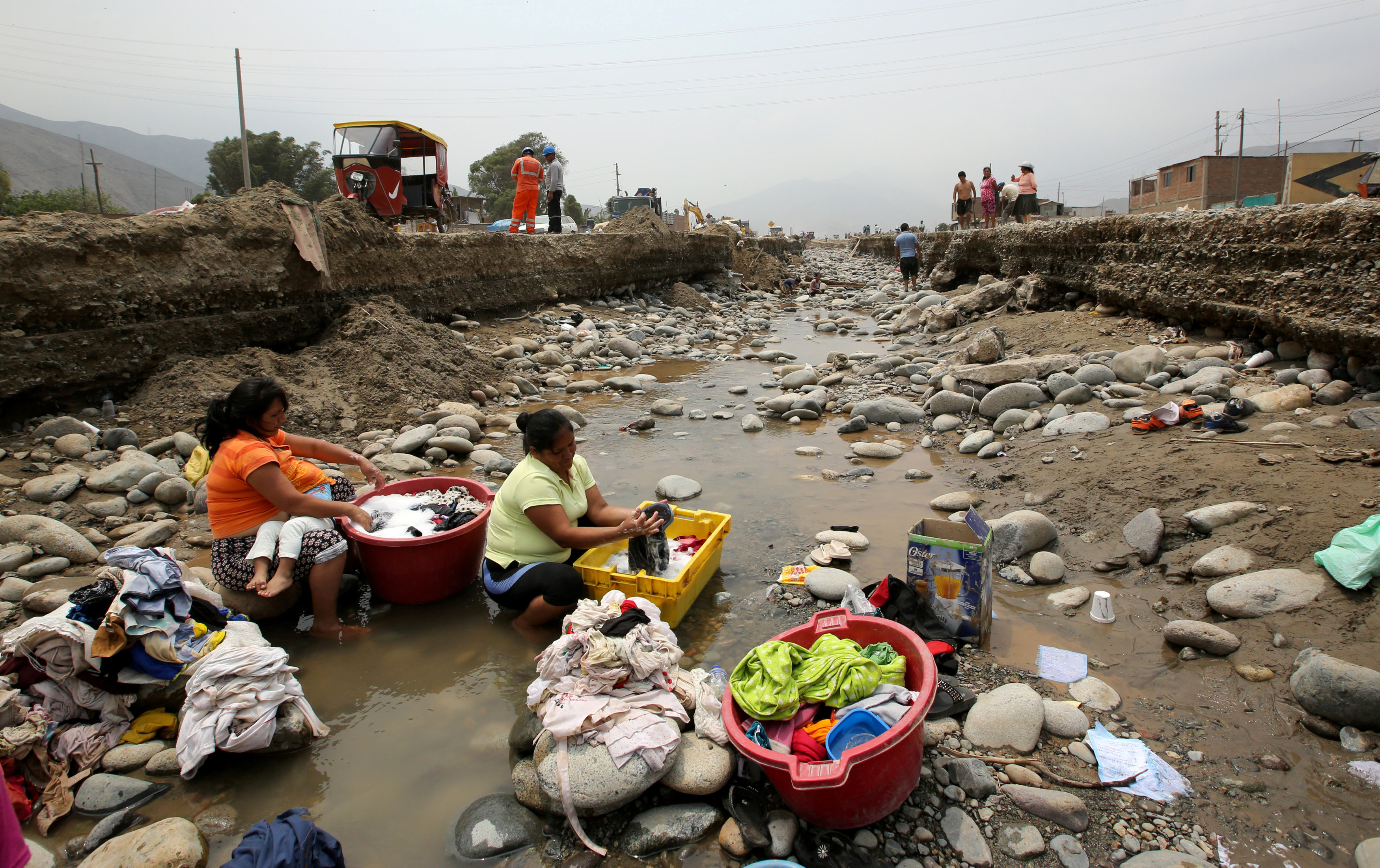 Residents do the laundry at a flooded Ramiro Priale highway, after rivers breached their banks due to torrential rains, causing flooding and widespread destruction in Huachipa, Lima, Peru, March 20, 2017. REUTERS/Mariana Bazo