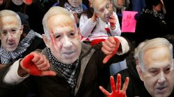 FILE PHOTO: Anti-Israel demonstrators led by the protest group Code Pink wear masks of Israeli Prime Benjamin Netanyahu as they sit at the entrance to the American Israel Public Affairs Committee (AIPAC) policy conference at the Washington Convention Center in Washington, March 1, 2015. REUTERS/Jonathan Ernst/File Photo