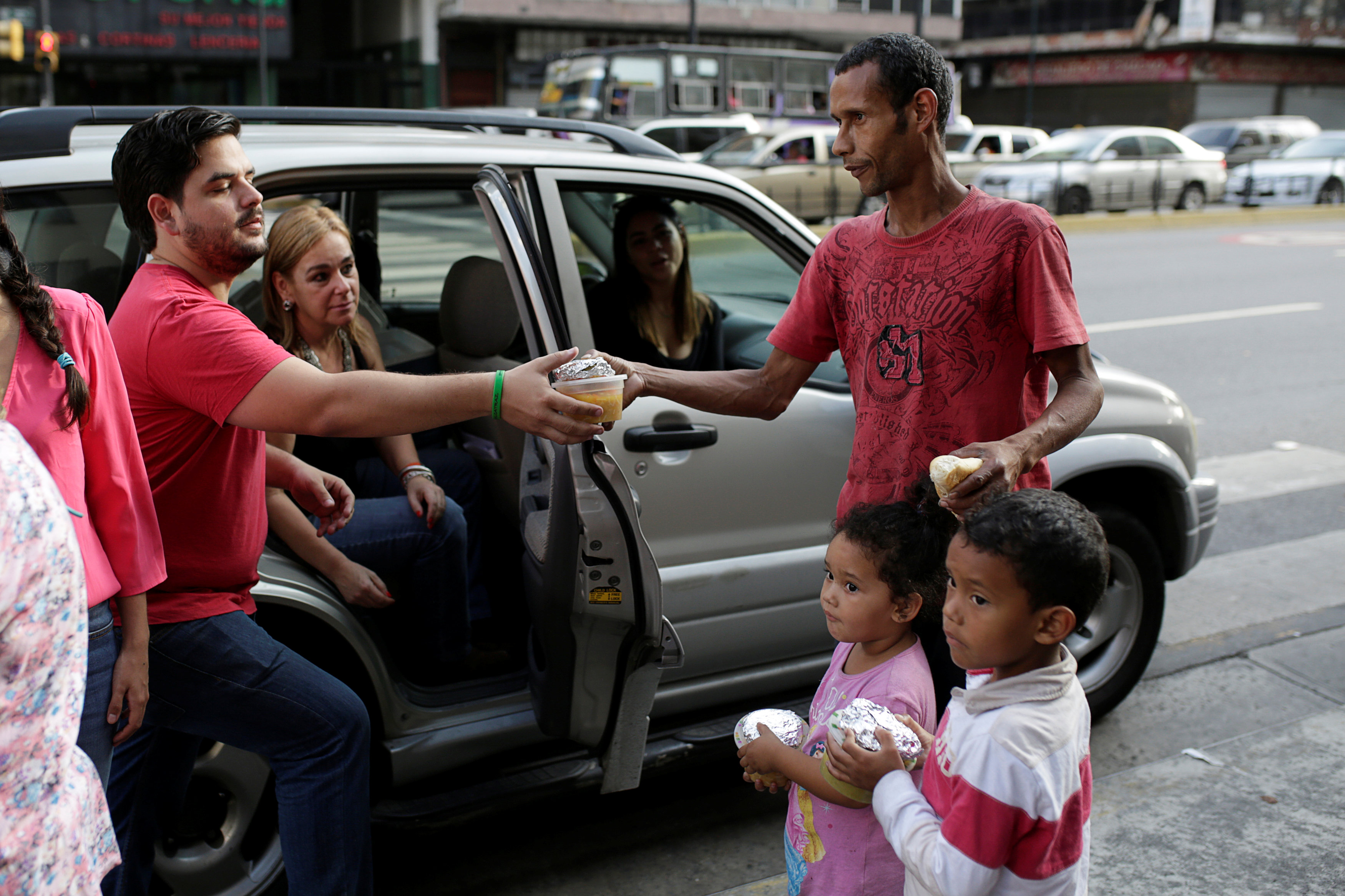 Diego Prada (L), a volunteer of the Make The Difference (Haz La Diferencia) charity initiative, gives a cup of soup and an arepa to a man in a street of Caracas, Venezuela March12, 2017. Picture taken March 12, 2017. REUTERS/Marco Bello