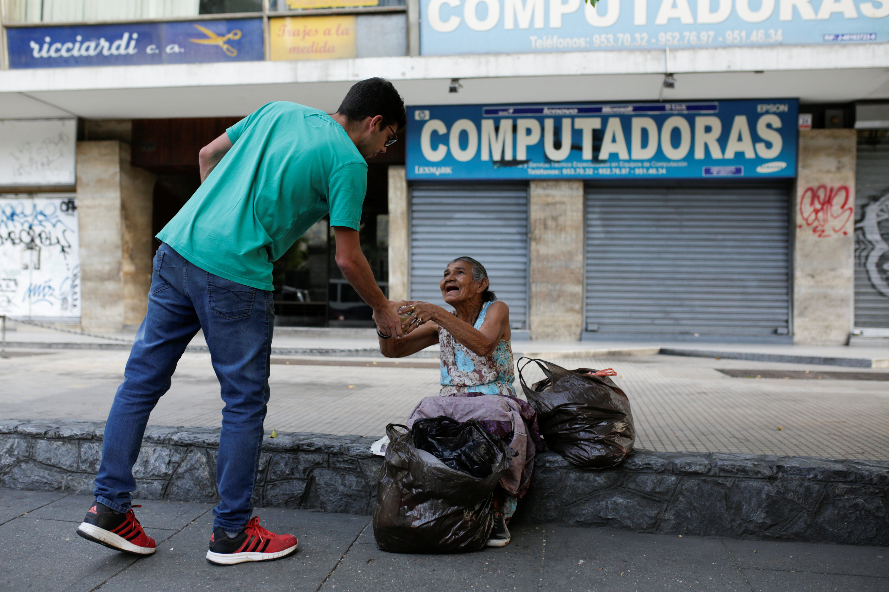 Mariano Marquez (L), a volunteer of Make The Difference (Haz La Diferencia) charity initiative, gives a cup of soup and an arepa to a homeless woman in a street of Caracas, Venezuela March12, 2017. Picture taken March 12, 2017. REUTERS/Marco Bello
