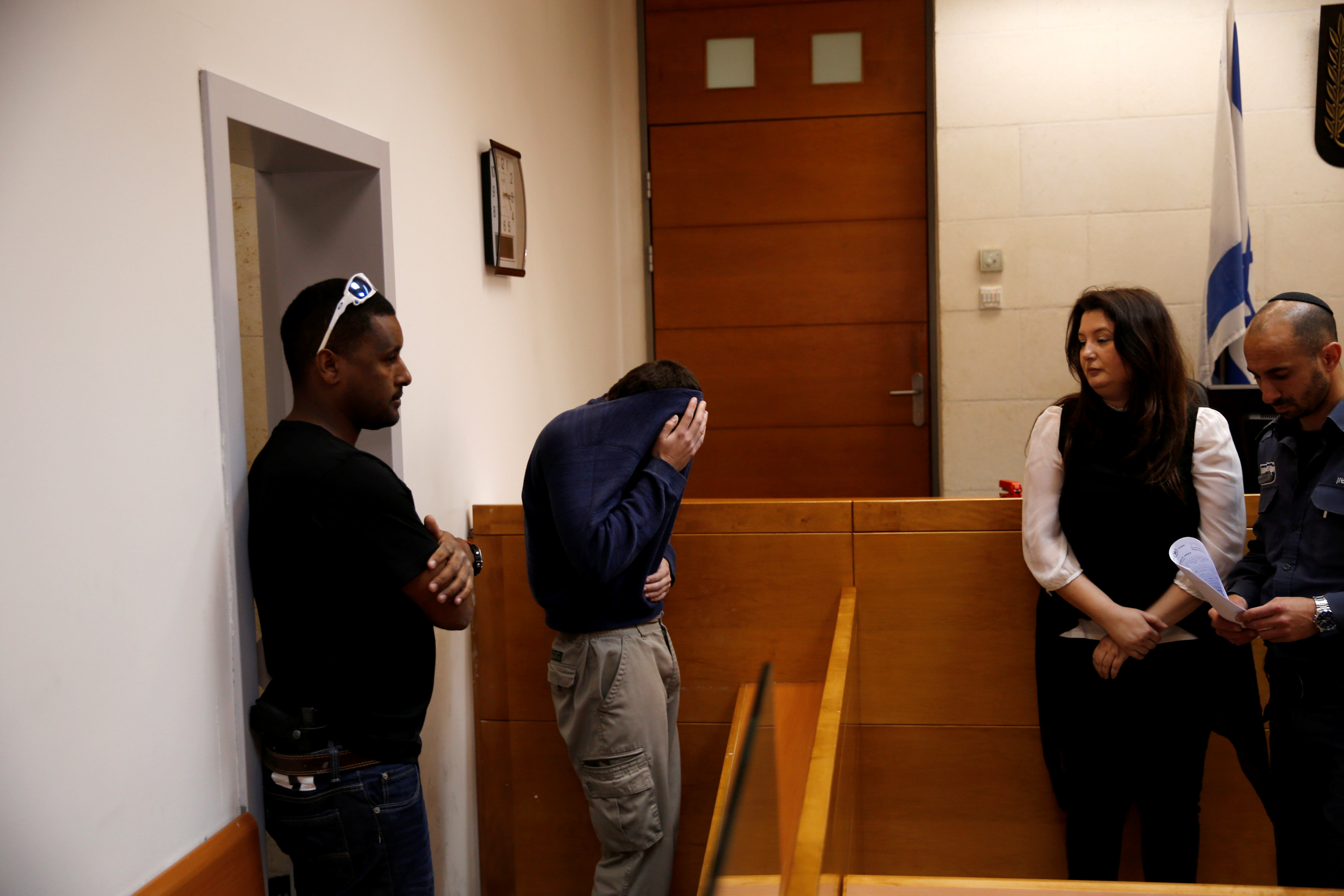 U.S.-Israeli teen (2ndL) arrested in Israel on suspicion of making bomb threats against Jewish community centres in the United States, Australia and New Zealand over the past three months, is seen before the start of a remand hearing at Magistrate's Court in Rishon Lezion, Israel March 23, 2017. REUTERS/Baz Ratner