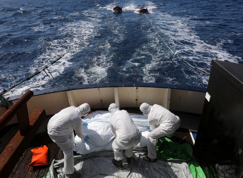 Lifeguards from the Spanish NGO Proactiva Open Arms sanitise five dead bodies of migrants on-board the former fishing trawler Golfo Azzurro following a search and rescue operation in central Mediterranean Sea off the Libyan coast, March 24, 2017. REUTERS/Yannis Behrakis