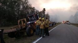 Firefighters and firefighting equipment arrive to deal with wildfire that quickly spread across acres of land, damaging many homes and forcing residents to evacuate in this image released on social media in Nassau County, Florida, U.S. on March 22, 2017. Courtesy Florida Forest Service/Handout via REUTERS