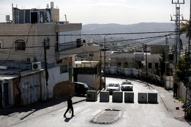 FILE PHOTO: A man walks next to a newly erected concrete barriers at the entrance to Jabel Mukaber, in an area of the West Bank that Israel captured in a 1967 war and annexed to the city of Jerusalem, the morning after a Palestinian rammed his truck into a group of Israeli soldiers on a popular promenade in Jerusalem January 9, 2017. REUTERS/Amir Cohen/File Photo