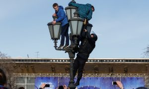A law enforcement officer climbs on a lamp pole to detain opposition supporters during a rally in Moscow. REUTERS/Sergei