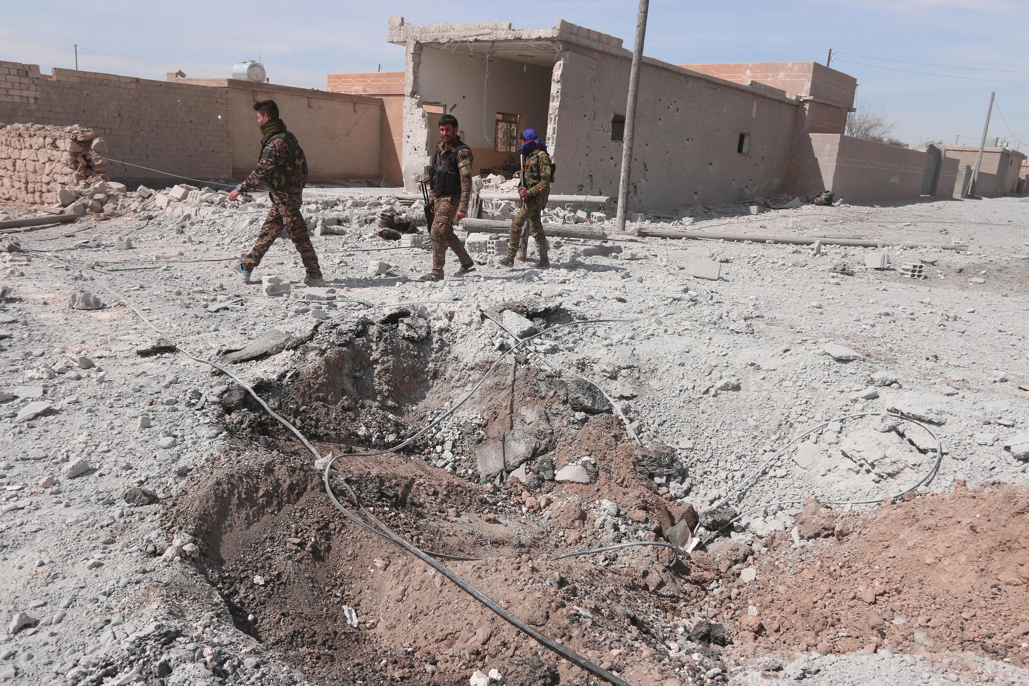 Syrian Democratic Forces (SDF) fighters walk near damaged ground east of Raqqa city, Syria.