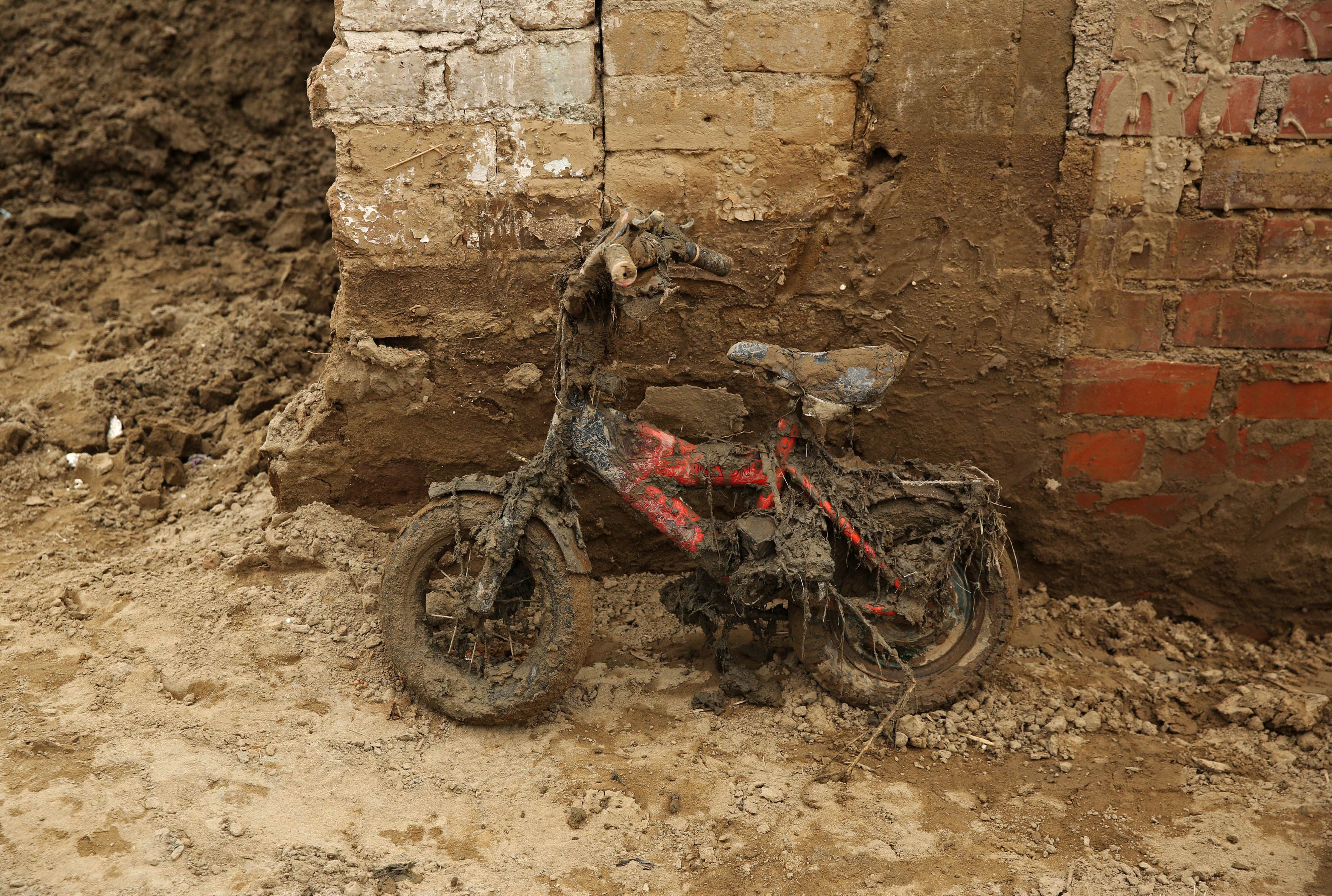 A children's bike leans against a wall covered in mud after rivers breached their banks due to torrential rains, causing flooding and widespread destruction in Carapongo Huachipa, Lima, Peru,