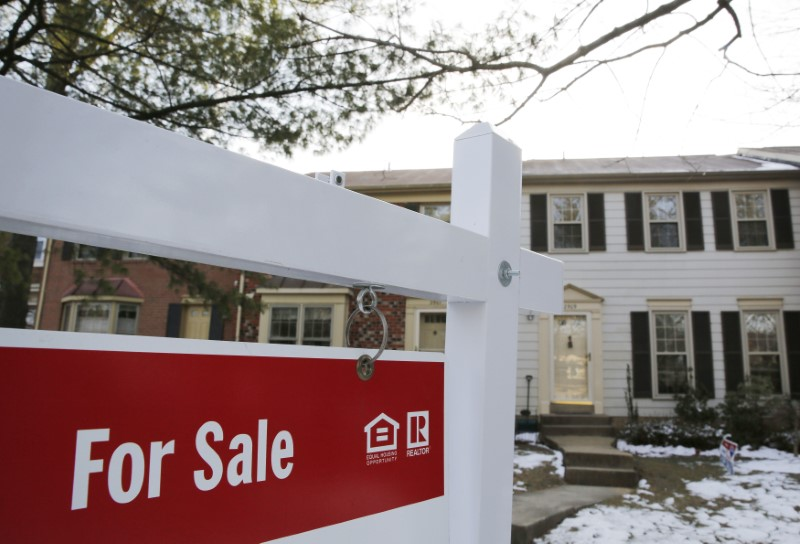 A home for sale sign hangs in front of a house in Oakton in Virginia March 27, 2014. REUTERS/Larry Downing