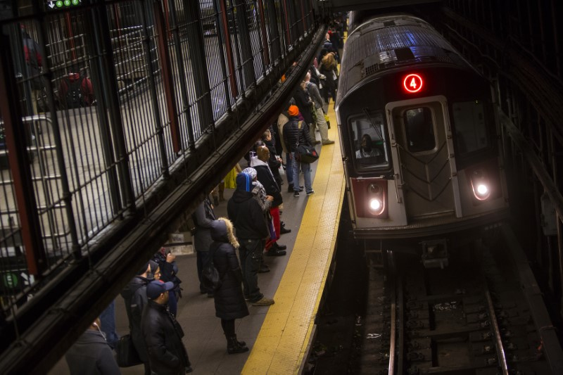 Commuters wait to ride New York City Subway in New York, December 12, 2013. REUTERS/Eric Thayer