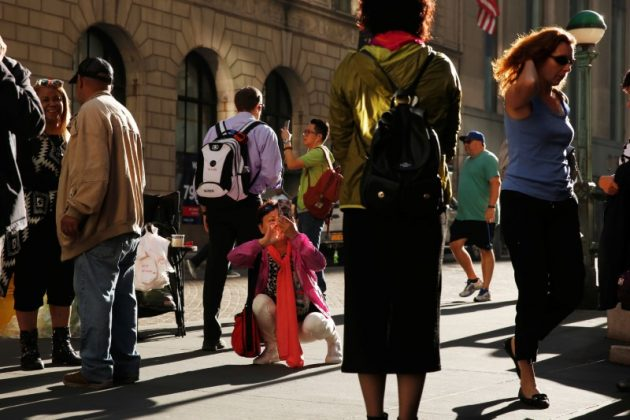 FILE PHOTO: A woman crouches down to take a cell phone photograph as pedestrians walk past in New York, U.S., October 19, 2016. REUTERS/Lucas Jackson