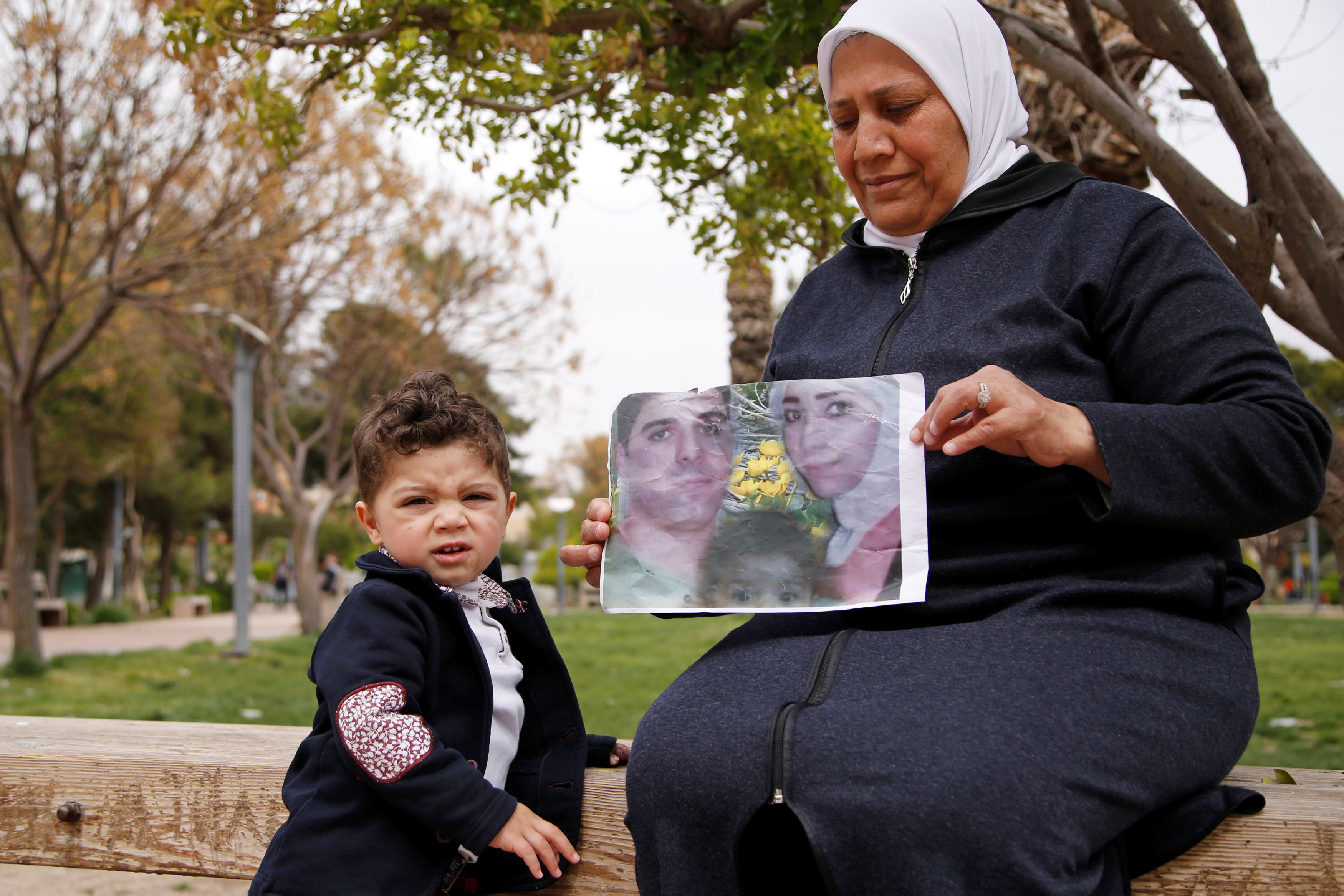 Hajar Saleh poses with her grandson Jaafar as she holds a picture depicting Jaafar's parents, Amina Saleh and her husband Imad Azouz who were killed fleeing Syria's civil war, at a garden in the Damascus district of Mezzeh,