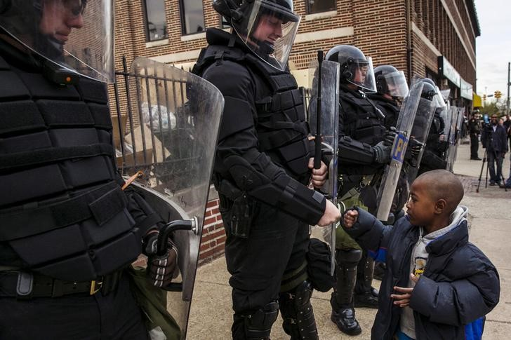 A young boy greets police officers in riot gear during a 2005 march in Baltimore. REUTERS/Lucas Jackson