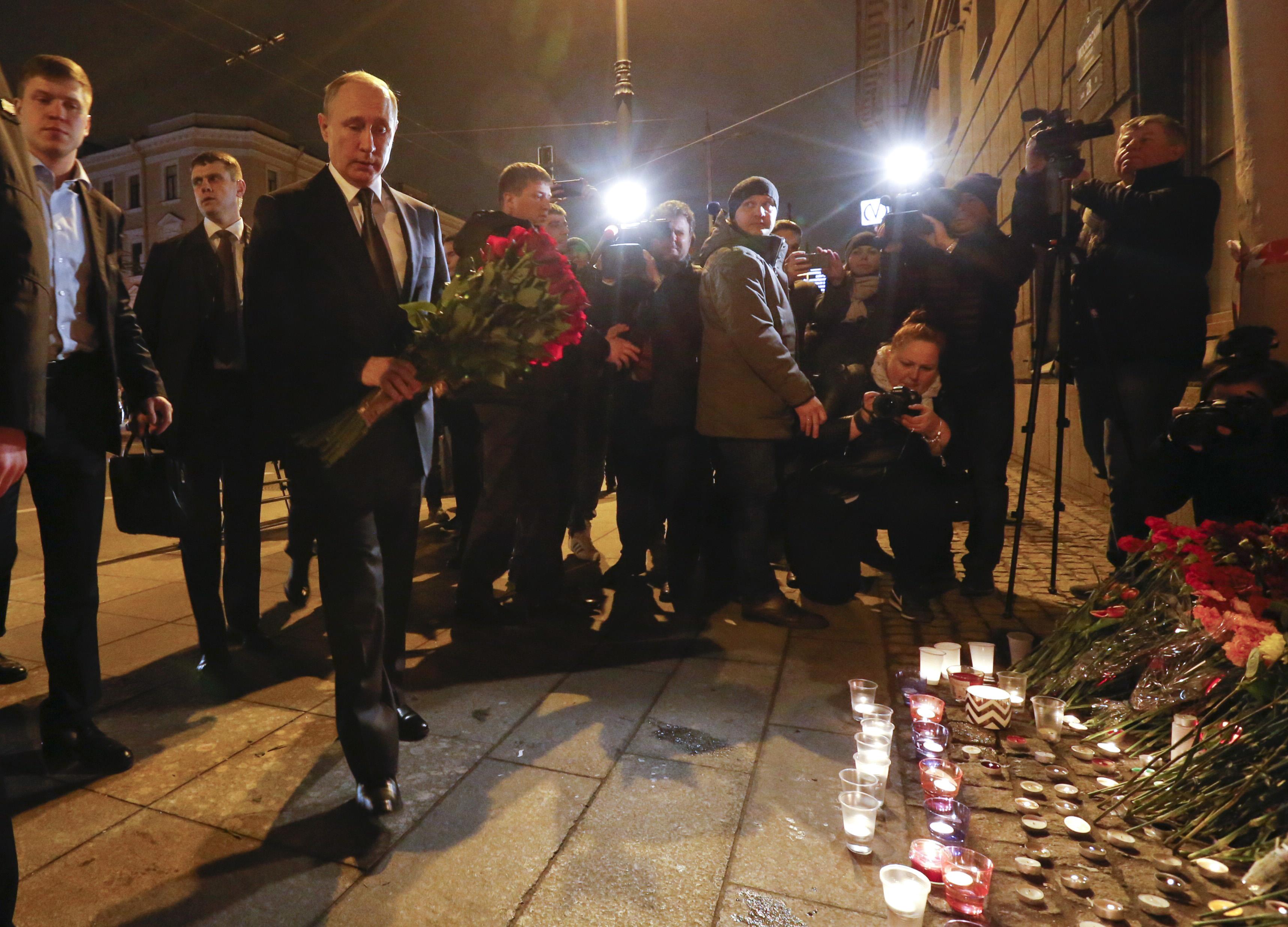 Russian president Vladimir Putin puts flowers down outside Tekhnologicheskiy Institut metro station in St. Petersburg, Russia. REUTERS/Grigory Duko