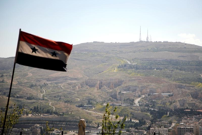 A Syrian national flag flutters as Qasioun mountain is seen in the background from Damascus, Syria April 7, 2017. REUTERS/Omar Sanadiki