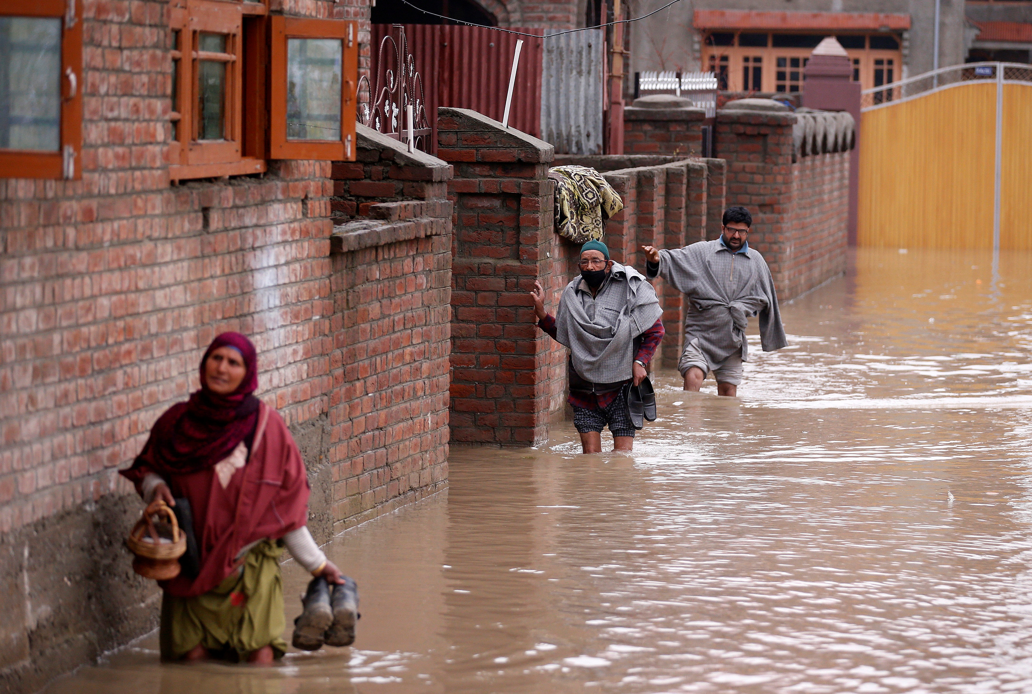 People wade through a flooded street after incessant rains in Srinagar April 7, 2017. REUTERS/Danish Ismail