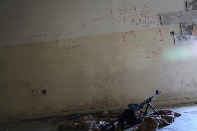 A machine gun is seen on the floor next to a map drawn to show distances, on the wall of a sniper's nest in a building controlled by Iraqi forces fighting the Islamic State in Mosul, Iraq, April 6, 2017. REUTERS/Andres Martinez Casares