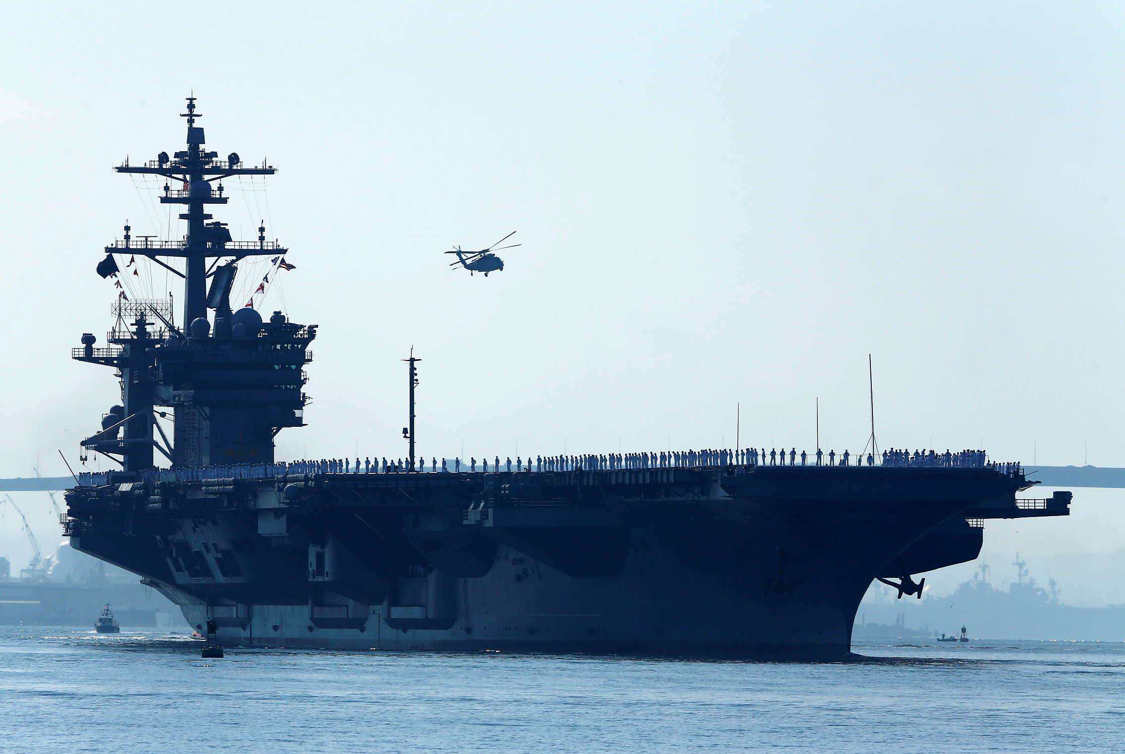 FILE PHOTO - Sailors man the rails of the USS Carl Vinson, a Nimitz-class aircraft carrier, as it departs its home port in San Diego, California August 22, 2014.