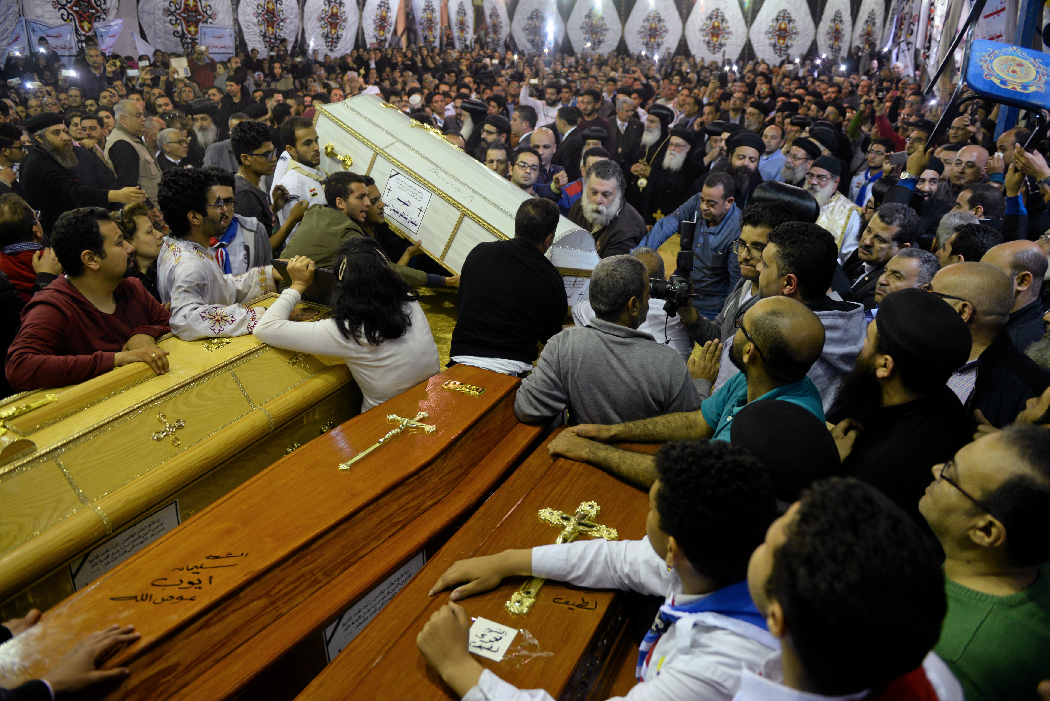 People watch as the coffins of victims arrive to the Coptic church that was bombed on Sunday, in Tanta, Egypt,
