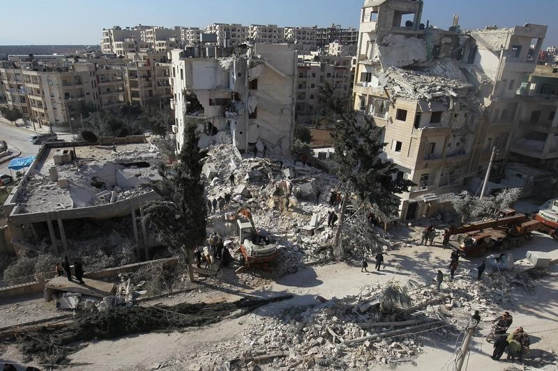 People inspect the damage at a site hit by airstrikes in the rebel-held city of Idlib, Syria