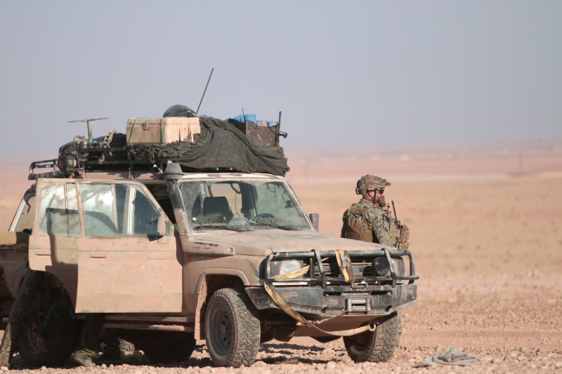 A U.S. fighter stands near a military vehicle, north of Raqqa city, Syria