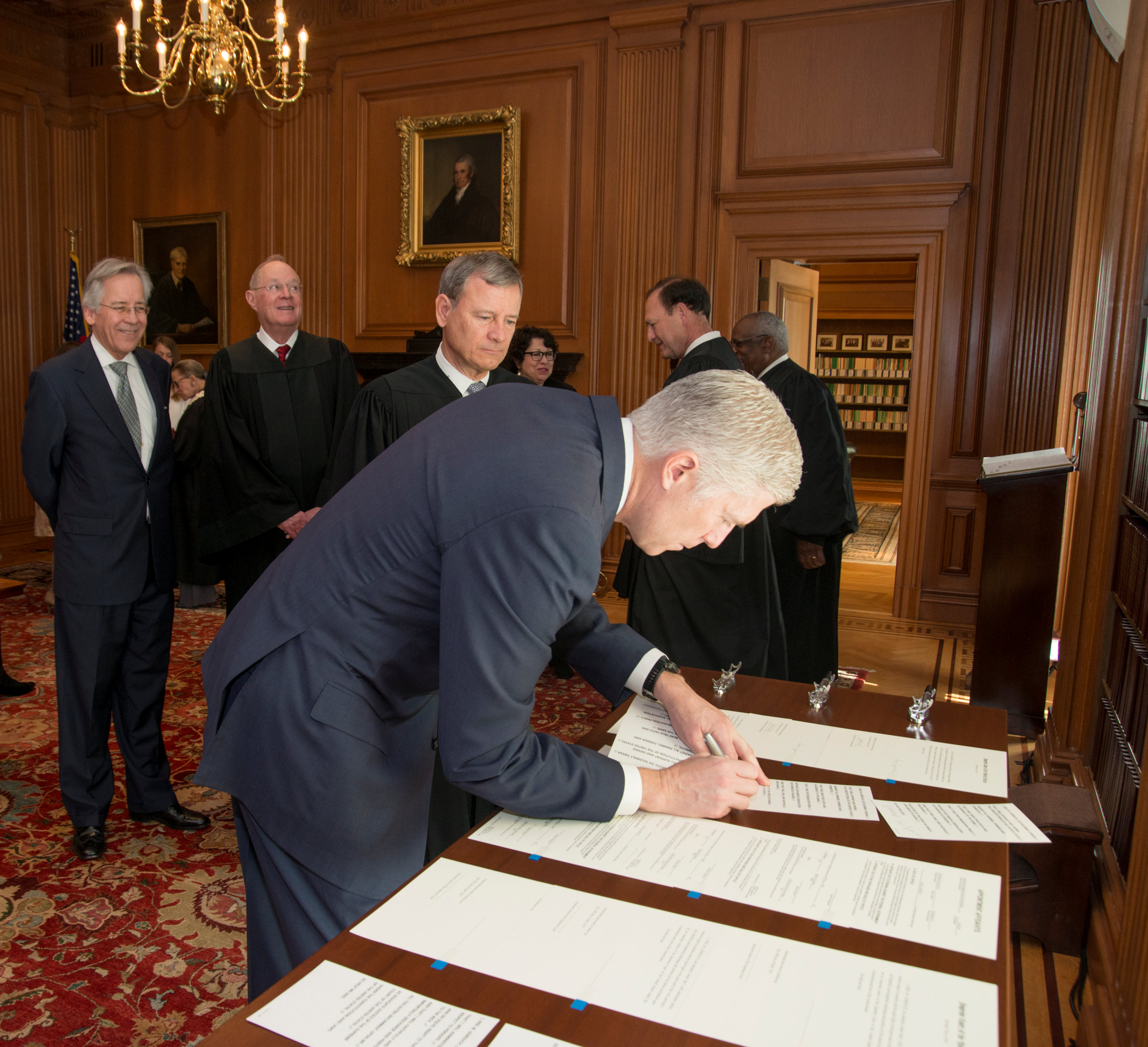 Chief Justice of the United States John Roberts (C) looks on as Judge Neil Gorsuch (R) signs the constitutional oath during swearing-in ceremony at the Supreme Court in Washington, U.S.