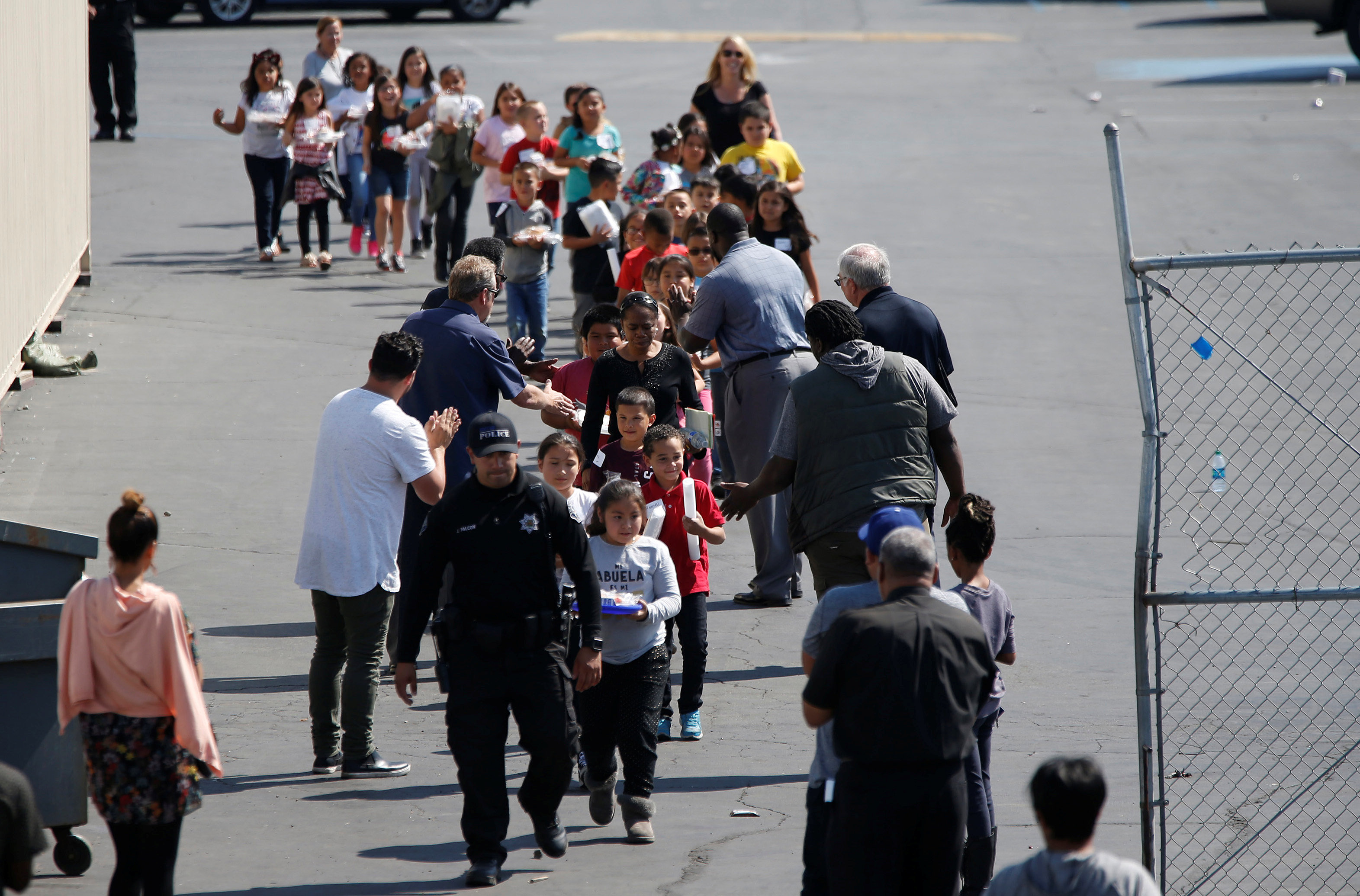 REFILE -- CORRECTING TYPO -- Students who were evacuated after a shooting at North Park Elementary School walk past well-wishers to be reunited with their waiting parents at a high school in San Bernardino, California, U.S. April 10, 2017. REUTERS/Mario Anzuoni