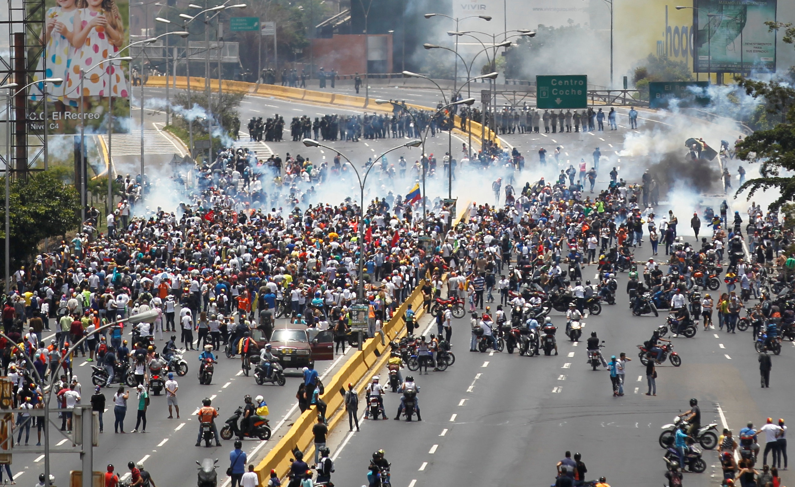 Demonstrators clash with riot police while ralling against Venezuela's President Nicolas Maduro's government in Caracas,